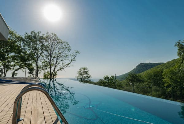 Luxury infinity pool in a backyard on a sunny day