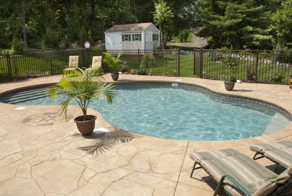 Curved concrete backyard pool surrounded by chairs.