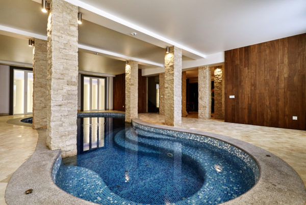 A blue indoor curved swimming pool.